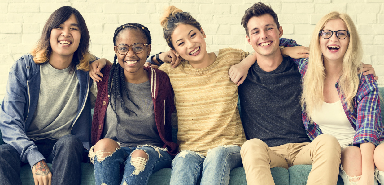 Five Teens sitting with arms around each other and smiling